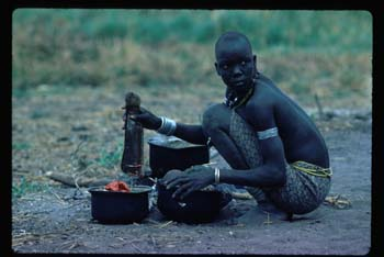 191Dinka woman squats as cooks fish040ZKR015